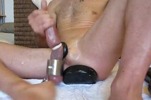 Hammering the silicone fake penis in a gay hole